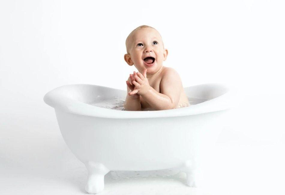 Baby sitzt in Mini Badewanne