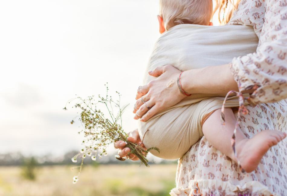 Mutter trägt Baby in Babytrage