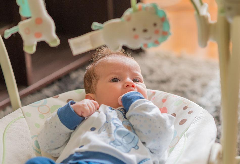 Baby liegt in elektrischer Babyschaukel